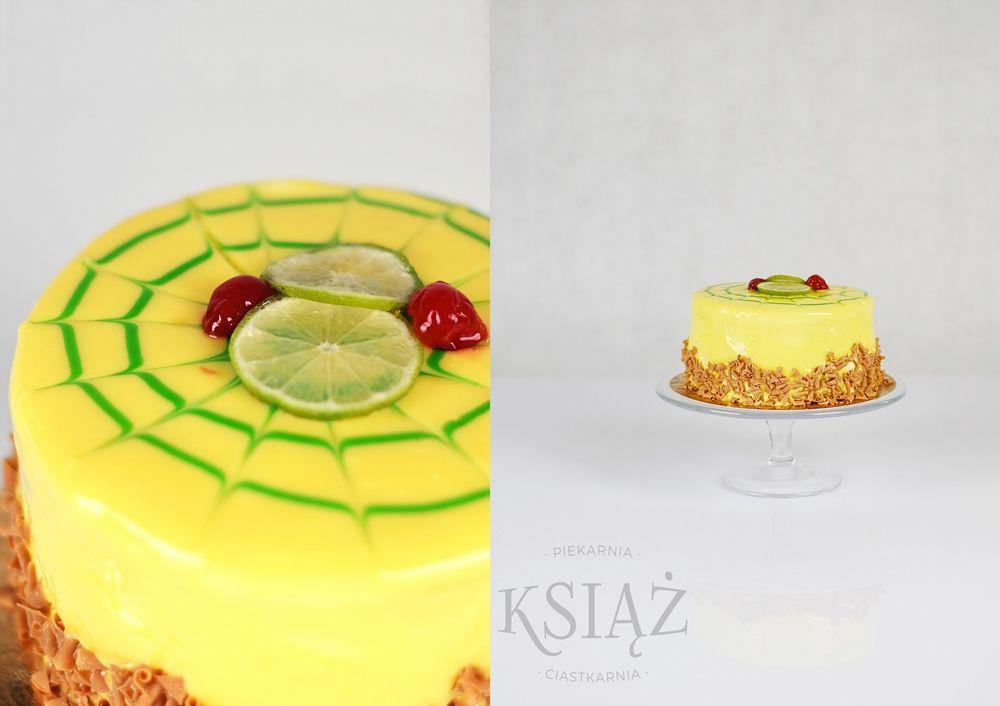 Tort limonkowy T024 - jasny biszkopt przełożony śmietaną limonkową, wykończony żelem i czekoladą