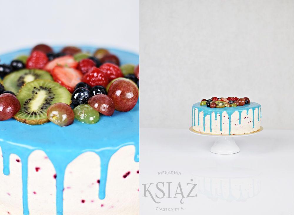 Tort Owocowy Ogród T018 - jasny biszkopt z delikatnym owocowym kremem, polany niebieską polewą na bazie białej czekolady wykończony owocami sezonowymi